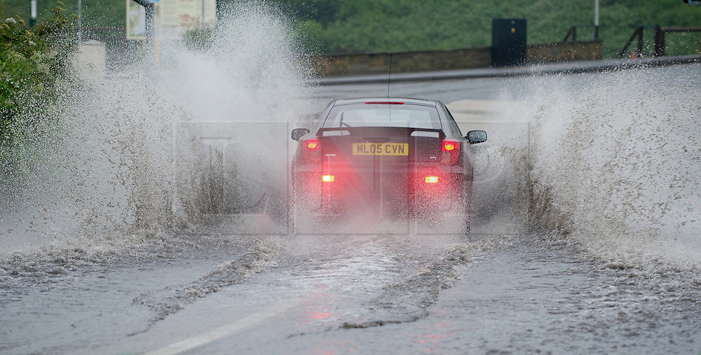 © Licensed to London News Pictures. 06/07/2012..Saltburn, Cleveland, England...After a night of heavy rain drivers on their way to work encounter deep puddles along the sea front road in Saltburn, Cleveland...Photo credit : Ian Forsyth/LNP