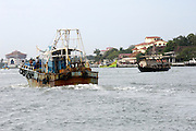 Thursday 14th August 2014: A fishing boat passes a ferry on the water near Fort Kochi.