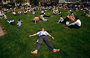 Having removed his shoes and socks, and with his wallet sitting on his stomach, a city office workers stretches out over the lush grass during a hot summer lunchtime in trinity Square in the City of London, England. With feet wide apart and arms spread, the young man is clearly fast asleep under a hot mid-day sun. Risking sunburn after prolonged solar radiation exposure, he is joined by dozens of other co-workers who also enjoy the inner-city heatwave.