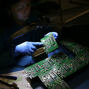 Hang Nguyen inspects circuit boards at ControlTek, a circuit board manufacturer in Vancouver, Wash., that has been affected by tariffs.<br /> <br /> For the first year of President Trump's trade war with China, many American manufacturers found ways to get by -- making contingency plans, but avoiding long-term changes in anticipation of a deal. But now with a deal seemingly a long way off, and tensions likely to continue regardless, companies are revisiting that approach. Electronics manufacturers are caught up not just in the tariffs but also in the national security fight over Huawei and other firms.