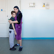 CAPTION: Kirill is cared for by his step-mother Tatiana, together with her partner, who is also a step-parent to him. His natural mother brought Kirill to her earlier relationship with that man, and then left him with him. Aged just 19 herself, Tatiana has three children, and has been caring for Kirill for the past three years. LOCATION: Volgograd City Hospital #1, Volgograd, Russia. INDIVIDUAL(S) PHOTOGRAPHED: Kirill Fedorenko (left) and Tatiana Fedorenko (right).