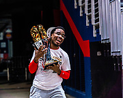 """After winning the 2020 NBA 2K League Championship, Wizards District Gaming small forward Maurice """"ReeseDaGood"""" Delaney runs into Capital One Arena with the trophy to celebrate on August 30, 2020."""
