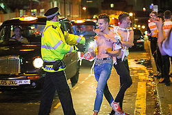 """© Licensed to London News Pictures . 16/11/2015 . Manchester , UK . Police push people back from the path of oncoming taxis . Annual student pub crawl """" Carnage """" at Manchester's Deansgate Locks nightclubs venue . The event sees students visit several clubs over the course of an evening . This year's theme is """" Animal Instinct - unleash your beast """" . Photo credit : Joel Goodman/LNP"""