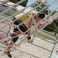 Competitor climbs a rope obstacle during the Brutal Run extreme obstacle course race in Budapest, Hungary on August 30, 2014. ATTILA VOLGYI
