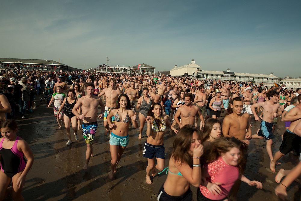 An enthusiastic crowd runs for the water at the annual Pier Swim, held at the Narragansett Town Beach on New Year's Day.