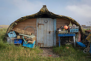 A disused boat now serving as a shed for a local fisherman sits upside down on the beach on Holy Island, on 27th September 2017, on Lindisfarne Island, Northumberland, England. Local fishermen on Holy Island considered it a sin to send boats to the junkyard. They instead found a way to transform their old herring boats into perfect little storage sheds for their nets, tools, and other equipment. The Holy Island of Lindisfarne, also known simply as Holy Island, is an island off the northeast coast of England. Holy Island has a recorded history from the 6th century AD; it was an important centre of Celtic and Anglo-saxon Christianity. After the Viking invasions and the Norman conquest of England, a priory was reestablished.