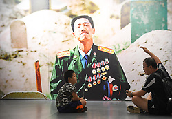(170730) -- BEIJING, July 30, 2017 (Xinhua) -- A visitor explains as a boy listens in front of a work displayed in a photo exhibition marking the 90th anniversary of the People's Liberation Army(PLA) in Beijing, capital of China, July 30, 2017.   (Xinhua/Chen Yehua)(clq) (Photo by Xinhua/Sipa USA)