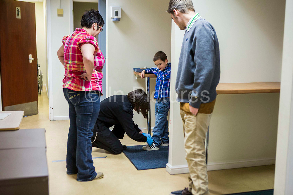 The partner and children of a prisoner go through the search process to get into a family visit session. HMP/YOI Portland, Dorset. A resettlement prison with a capacity for 530 prisoners. Dorset, United Kingdom.