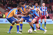 Tommy Rowe of Scunthorpe United under attack from Nat Knight-Percival of Shrewsbury Town during the Sky Bet League 1 match between Scunthorpe United and Shrewsbury Town at Glanford Park, Scunthorpe, England on 17 October 2015. Photo by Ian Lyall.
