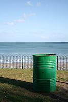 Green rubbish bin at Killiney beach in Dublin Ireland