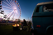 January 22-25, 2015: Rolex 24 hour. A fan keeps warm by a fire before sunrise on sunday morning.