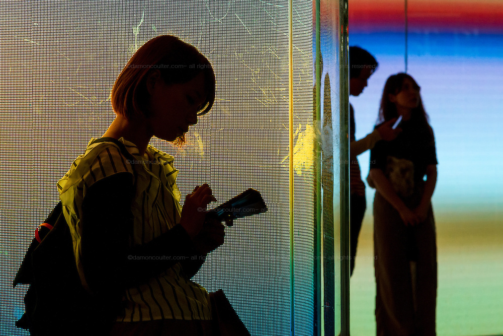 A young woman, in silhouette, uses a smart phone outside a colourful store in Shibuya, Tokyo, Japan. Friday September 23rd 2016