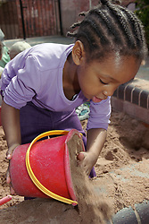 Nursery school girl playing with bucket and sand in playground sandpit,