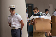 Incoming Citadel freshman known as knobs carries his newly issued gear watched by upperclassmen during matriculation day on August 17, 2013 in Charleston, South Carolina. The Citadel is a state military college that began in 1843.