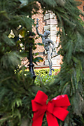 A statue of the Greek god Mercury framed by a Christmas wreath on Meeting Street in Charleston, SC.