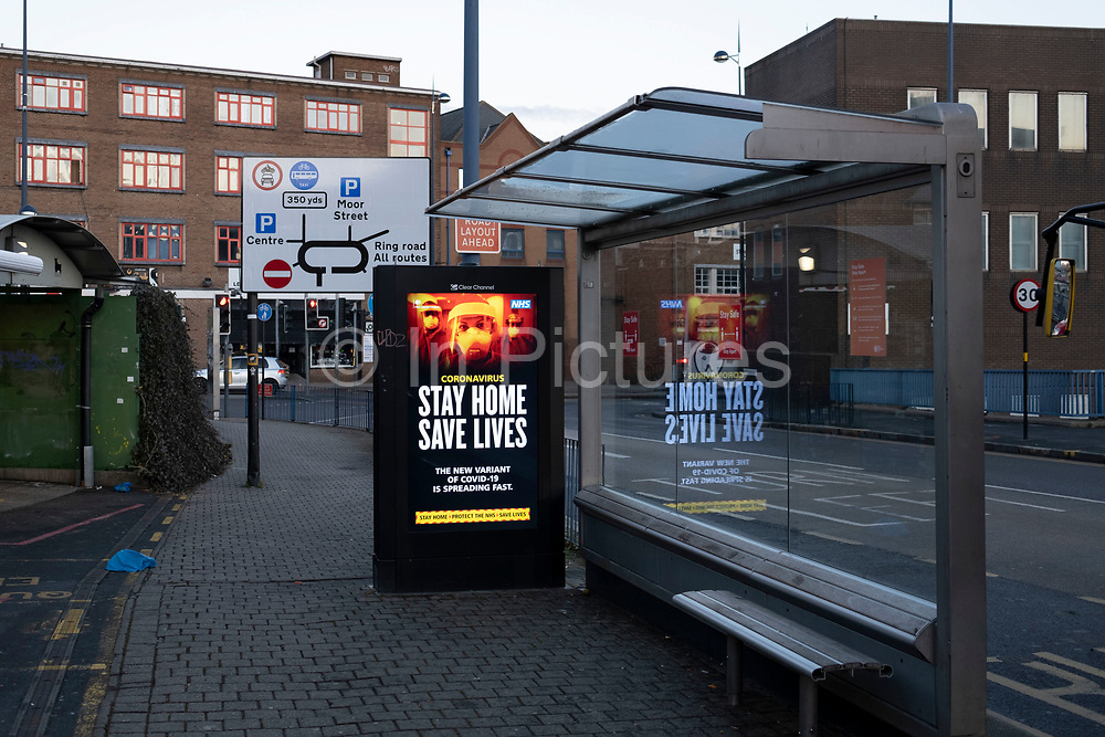 HM Government, and NHS advertising boards advice to stay at home and help save lives at a bus stop during the third national coronavirus lockdown in Birmingham city centre, which is deserted apart from a few people on 7th January 2021 in Birmingham, United Kingdom. Following the recent surge in cases including the new variant of Covid-19, this nationwide lockdown, which is an effective Tier Five, came into operation yesterday, with all citizens to follow the message to stay at home, protect the NHS and save lives.