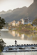 Tourist crossing river with stepping stones and view of the houses and Chinese style architecture in Zhangjiajie city in the background, Hunan Province, China