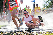 Lisa Darrah tumbles through a Slip 'n Slide at the 2012 Bolder Boulder 10K road race in Boulder, Colorado.