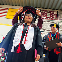 121213       Brian Leddy<br /> Navajo Technical University student Adriane Tenequer is hooded during graduation ceremonies in Chinle Friday. The graduation was the first for the school as a university.