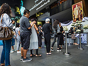 15 OCTOBER 2016 - BANGKOK, THAILAND: People stand in line at Siam Square, a shopping mall in Bangkok, to sign a condolences book for Bhumibol Adulyadej, the King of Thailand. King Bhumibol Adulyadej died Oct. 13, 2016. He was 88. His death comes after a period of failing health. With the king's death, the world's longest-reigning monarch is Queen Elizabeth II, who ascended to the British throne in 1952. Bhumibol Adulyadej, was born in Cambridge, MA, on 5 December 1927. He was the ninth monarch of Thailand from the Chakri Dynasty and is known as Rama IX. He became King on June 9, 1946 and served as King of Thailand for 70 years, 126 days. He was, at the time of his death, the world's longest-serving head of state and the longest-reigning monarch in Thai history.      PHOTO BY JACK KURTZ