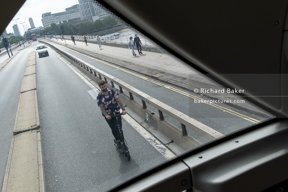 A man rides an eScooter over Waterloo Bridge  ahead of light traffic and few cars during the Coronavirus pandemic when many London workers are still working from home, on 20th August 2020, in London, England