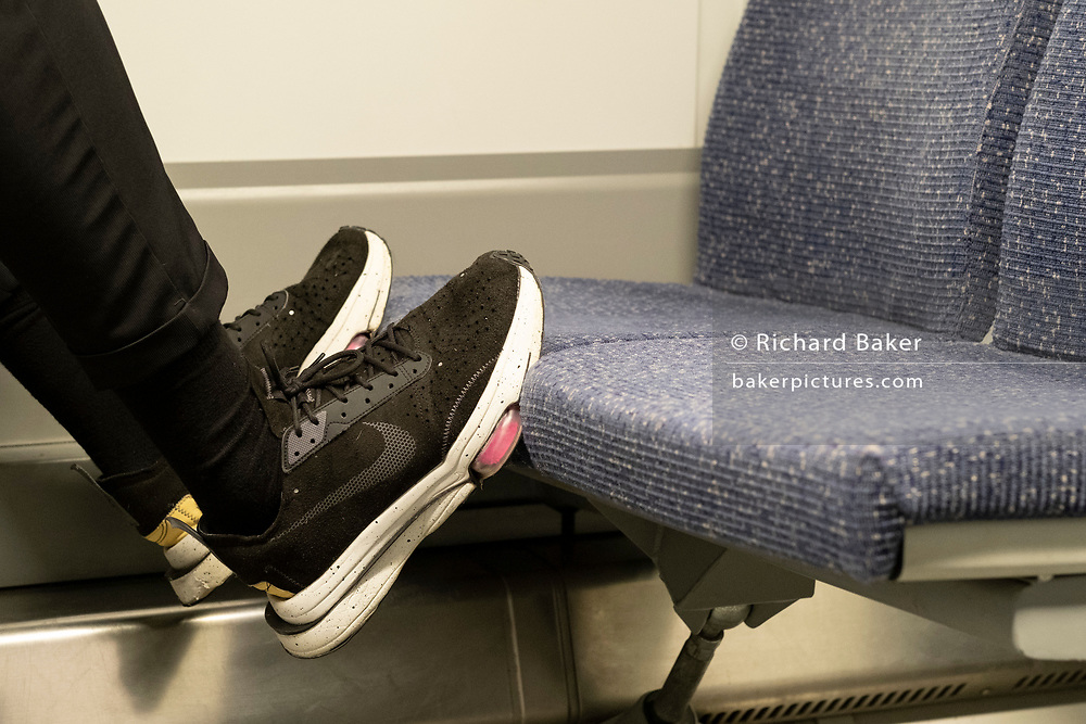The shoes of a rail passenger rest on the fabric seats of train travelling through south London, on 26th February 2021, in London, England. Rail and Tube passengers who put feet on seats or play music too loudly face £50 on-the-spot fines from British Transport Police.