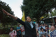 A man wearing a Shinzo Abe mask with a Hitler mustache attached gives a nazi salute at a demo outside the Japanese parliament building against Prime Minister, Shinzo Abe and his reinterpretation of Article 9 of the Japanese Constitution. Nagatacho, Tokyo, Japan. Friday July 17th 2015. Around 10,000 people took part to protest a change in the law that would allow collective self-defence which was ratified in the Lower House on Thursday. Many fear this new interpretation of Japan's unique peace constitution will mean Japanese soldiers being sent to war, to aid allies such as America,