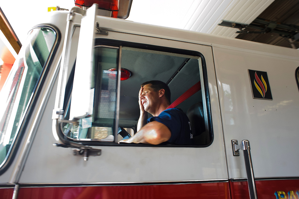 (photo by Matt Roth).Assignment ID: 30127696A.Wednesday, June 20, 2012..Baltimore City Truck Company 15 EVD Keith Rider wipes the sweat from his brow before leaving the station on a call Wednesday, June 20, 2012...City Councilman William Pete Welch proposes advertisements be allowed on Baltimore City Fire Department vehicles as a way to combat a $48 million budget shortfall, rather than disbanding three companies, including Truck Company 15, which services East Baltimore.