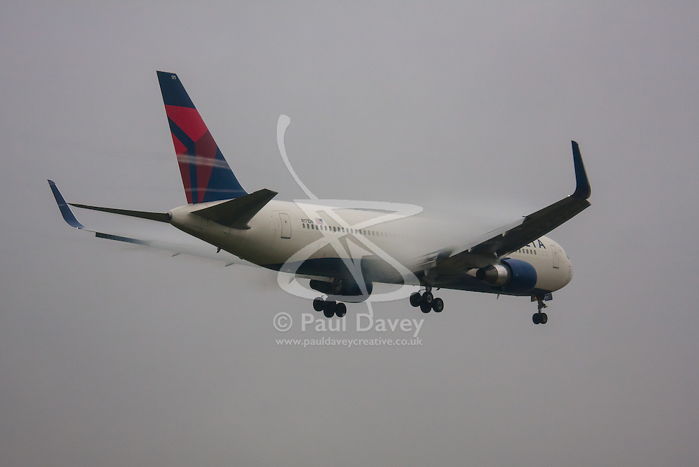 """January 3rd 2015, Heathrow Airport, London. Low cloud and rain provide ideal conditions to observe wake vortexes and """"fluffing"""" as moisture condenses over the wings of landing aircraft. With the runway visible only at the last minute, several planes had to perform a """"go-round"""", abandoning their first attempts to land. PICTURED: Water vapour streams from the control surfaces of a Delta  Boeing 767 as it prepares to land on Heathrow Airport's runway 27L."""