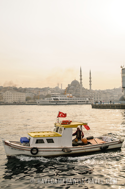 Boat on the Golden Horn going under the Galata Bridge with the Hidayet Mosque in the background.