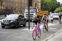 © London News Pictures. 25/08/2016. Cyclists pass through a red light while using a cycle lane on Abingdon Street. Cyclists repeatedly ignore new cycle lanes installed around westminster in central London. Between the hours of 8am and 9am on Wednesday 24/08/2016, 266 (two hundred and sixty six) cyclists passed through the red light at one of the newly installed  bike lanes and only 15 (fifteen) cyclists stopped.  The light system is designed to allow either vehicles or cyclists to pass at one time in order to make the junction safer for cyclists..... **VIDEO AVAILABLE** Photo credit: London News Pictures.