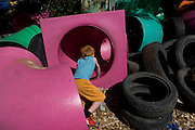 Boy climbs through tunnels in risk averse playground called The Land on Plas Madoc Estate, Ruabon, Wrexham, Wales. <br /> <br /> From the chapter entitled 'Playing with Fire' from the book 'Risk Wise: Nine Everyday Adventures' by Polly Morland (Allianz, The School of Life, Profile Books, 2015).