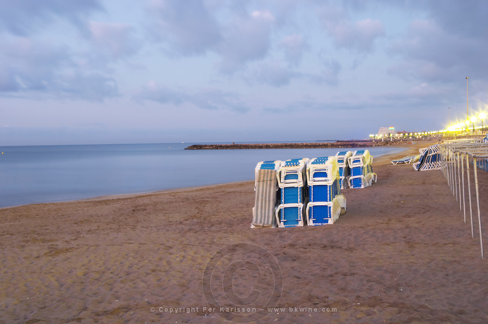 The beach. Deck chairs piled for the night. Sitges, Catalonia, Spain