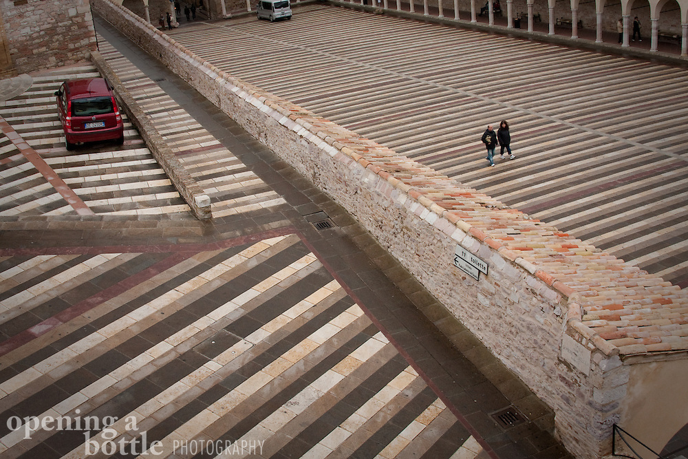 Pedestrians walk across the striped passageway of Piazza Inferiore di San Francesco, near the Church of St. Francis, Assisi, Umbria, Italy.
