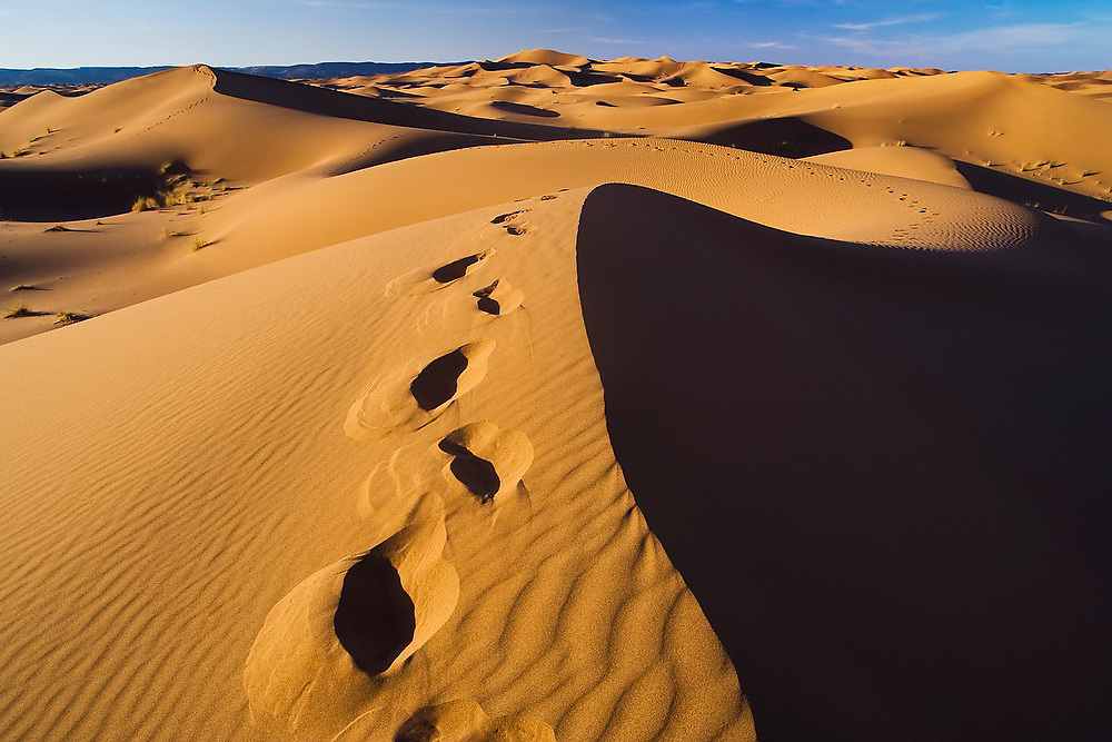 A trail of footsteps in the sand weaves away over and through the expansive sand dunes of Erg Zehar, near M'hamid, Morocco.