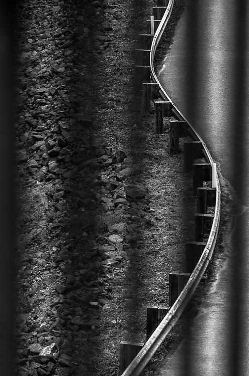 Road guard rail view through bridge railing, afternoon overcast, August, Clallam County, Olympic Peninsula, Washington, USA