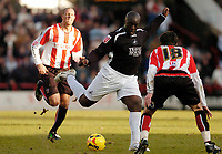 Photo: Leigh Quinnell.<br /> Brentford v Swansea City. Coca Cola League 1.<br /> 26/12/2005. Swanseas Adebayo Akinfenwa fires a shot past Brentfords Sam Tillen.