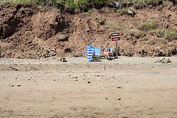 """A female Holiday maker with wind break and deckchairs sun bathes beside a """"Beware Dangerous Cliffs"""" sign  on the Beach during the May Bank Holiday. Filey, North Yorkshire<br />  <br /> 21 May 2013<br /> Image © Paul David Drabble<br /> www.pauldaviddrabble.co.uk"""