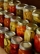 Jars of home canned gingered peaches, plums, pickled zucchinis, tomatoes, and other summer produce.