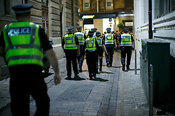 © Licensed to London News Pictures. 19/09/2014. Glasgow, UK. Police officers walking in an alleyway to separate pro-unionists and Scottish independence supporters at George Square in Glasgow as Scotland decides to stay in the union and First Minister Alex Salmond resigns over the results of the Scottish independence referendum on Friday, 19 September 2014. Photo credit : Tolga Akmen/LNP