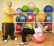 Jim Caruso, left, a certified fitness therapist and sports performance trainer, works with Debbie Hauser-Rand as she at Pure Symmetry Fitness in Pine Bush on Jan. 3, 2007. Hauser-Rand owns Pure Symmetry Fitness.
