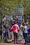 Two woman paying homage to Prince at the memorial fence which surrounds Paisley Park Studios. Chanhassen Minnesota MN USA