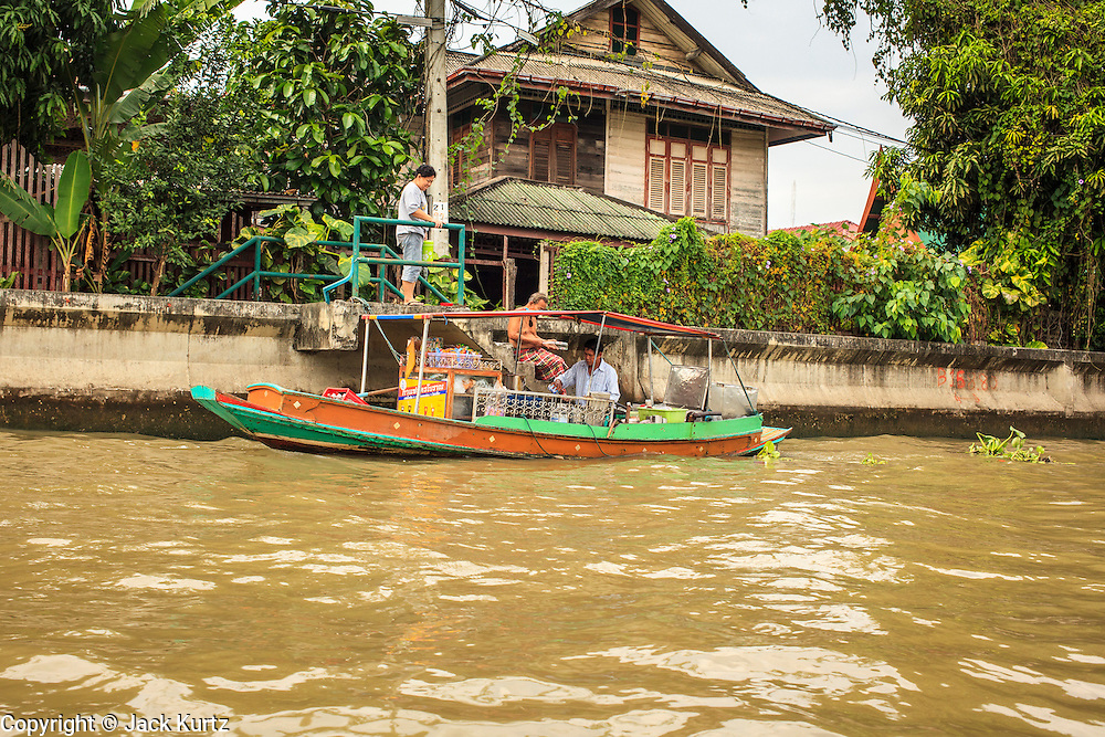 """17 NOVEMBER 2012 - BANGKOK, THAILAND:  A boat that serves a food stand makes a delivery to a home on a khlong or canal in the Thonburi section of Bangkok. Bangkok used to be known as the """"Venice of the East"""" because of the number of waterways the criss crossed the city. Now most of the waterways have been filled in but boats and ships still play an important role in daily life in Bangkok. Thousands of people commute to work daily on the Chao Phraya Express Boats and fast boats that ply Khlong Saen Saeb or use boats to get around on the canals on the Thonburi side of the river. Boats are used to haul commodities through the city to deep water ports for export.    PHOTO BY JACK KURTZ"""