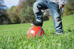 Close up small boy stepping on red football meadow