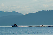 Water skier and speed boat on calm water in morning, South Shore, Lake Tahoe, from Kiva Beach, California