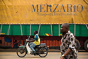 A man rides a motorcycle past a truck at the sea port in Lome, Togo on Friday October 3, 2008.