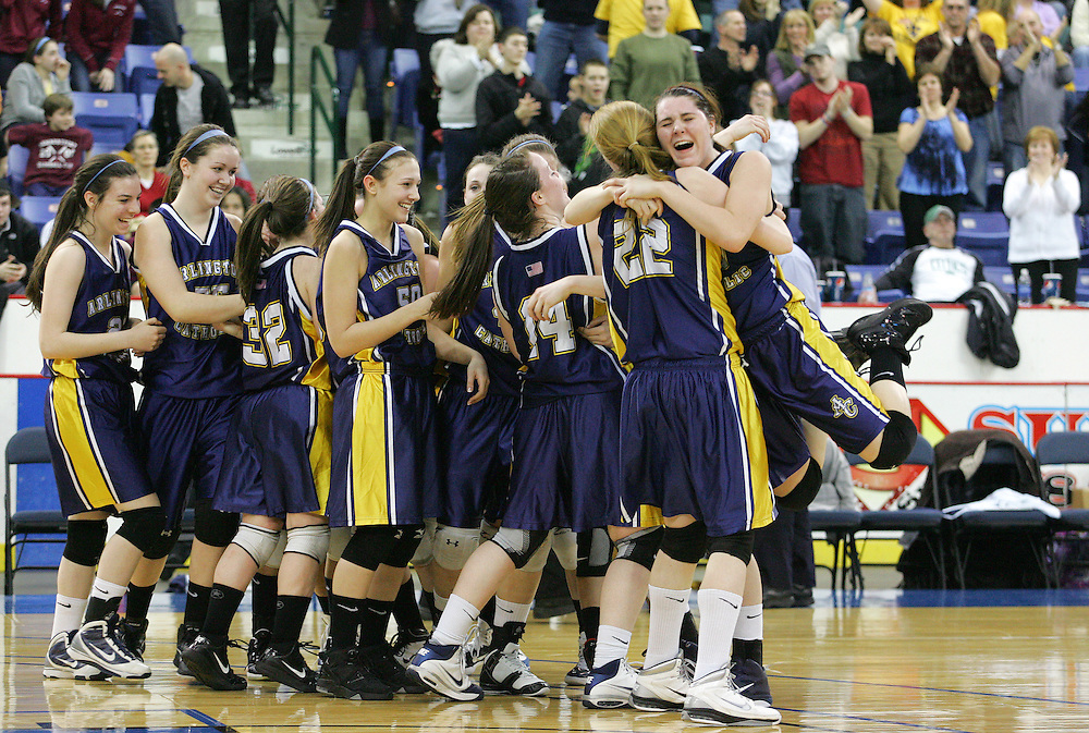 Lowell, MA 03/12/2011<br /> Arlington Catholic's Erin Klein jumps into the arms of teammate Kayla Awiszus as the Cougars celebrate their victory over Gloucester in the MIAA North Sectional Basketball Championships on Saturday night at the Tsongas Center in Lowell.
