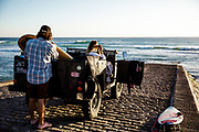 Couple parked in their landrover on the slipway at St Ouen's Bay, Jersey, CI, with the lady taking photos of the sea and surf and the man preparing his surfboard.