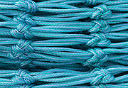 Colorful aqua and blue colored commercial fish nets with horizontal lines and diagonal knots create interesting patterns
