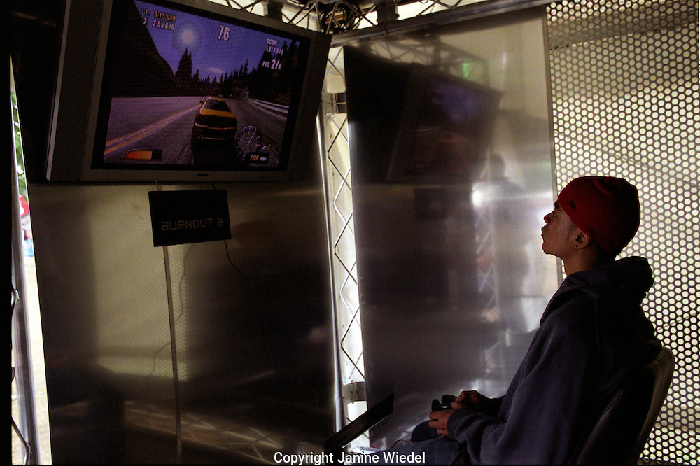 Young man playing on a playstation plasma screen.